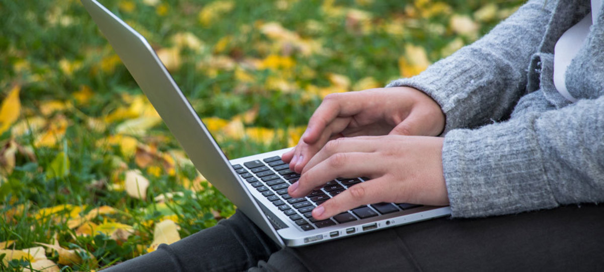 person with laptop on grass
