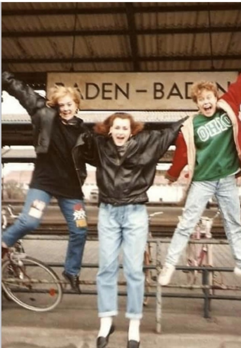 3 girls jumping in front of Baden Baden train station sign