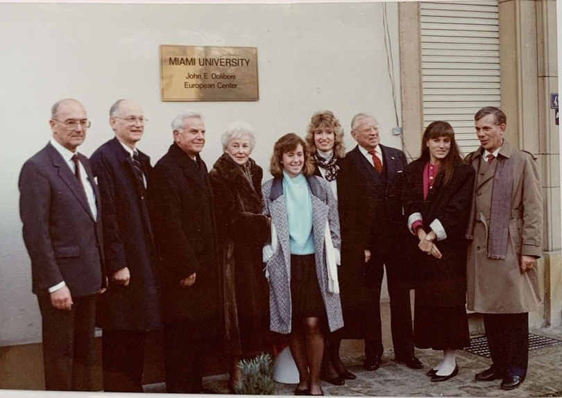 Miami officials and John Dolibois and family in front of the plaque bearing his name