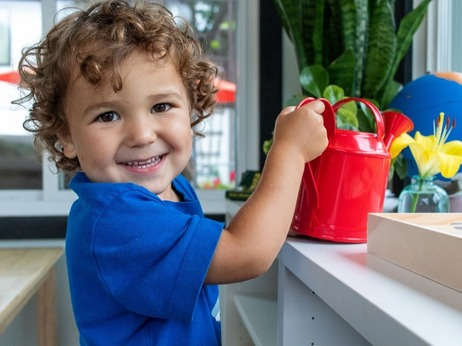 preschooler smiling at camera holding a watering can