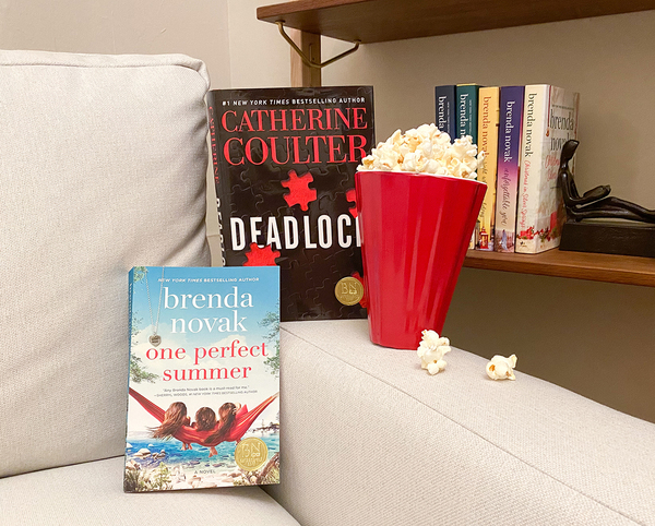 Two books on a couch with a container of popcorn