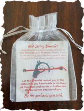 A picture of the Red String Bracelet in its packaging, a white translucent fabric drawstring bag.