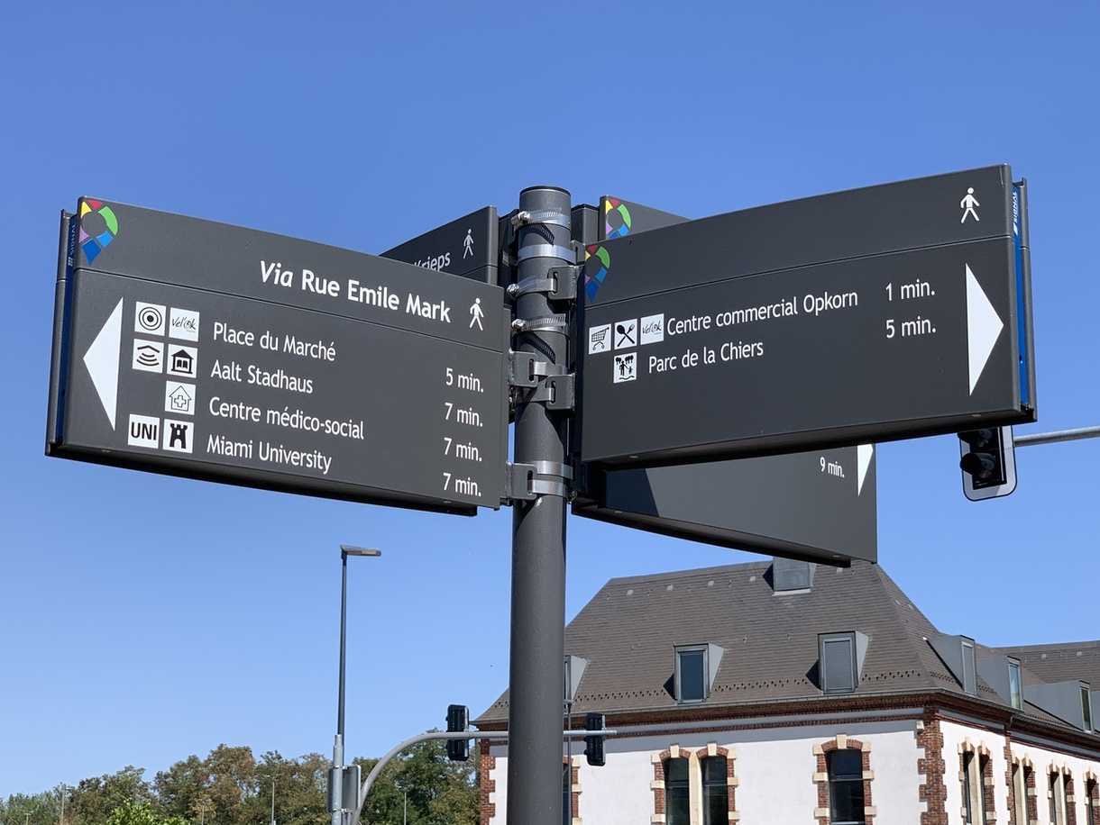 Signs on the street in Differdange pointing out walking distances to different places