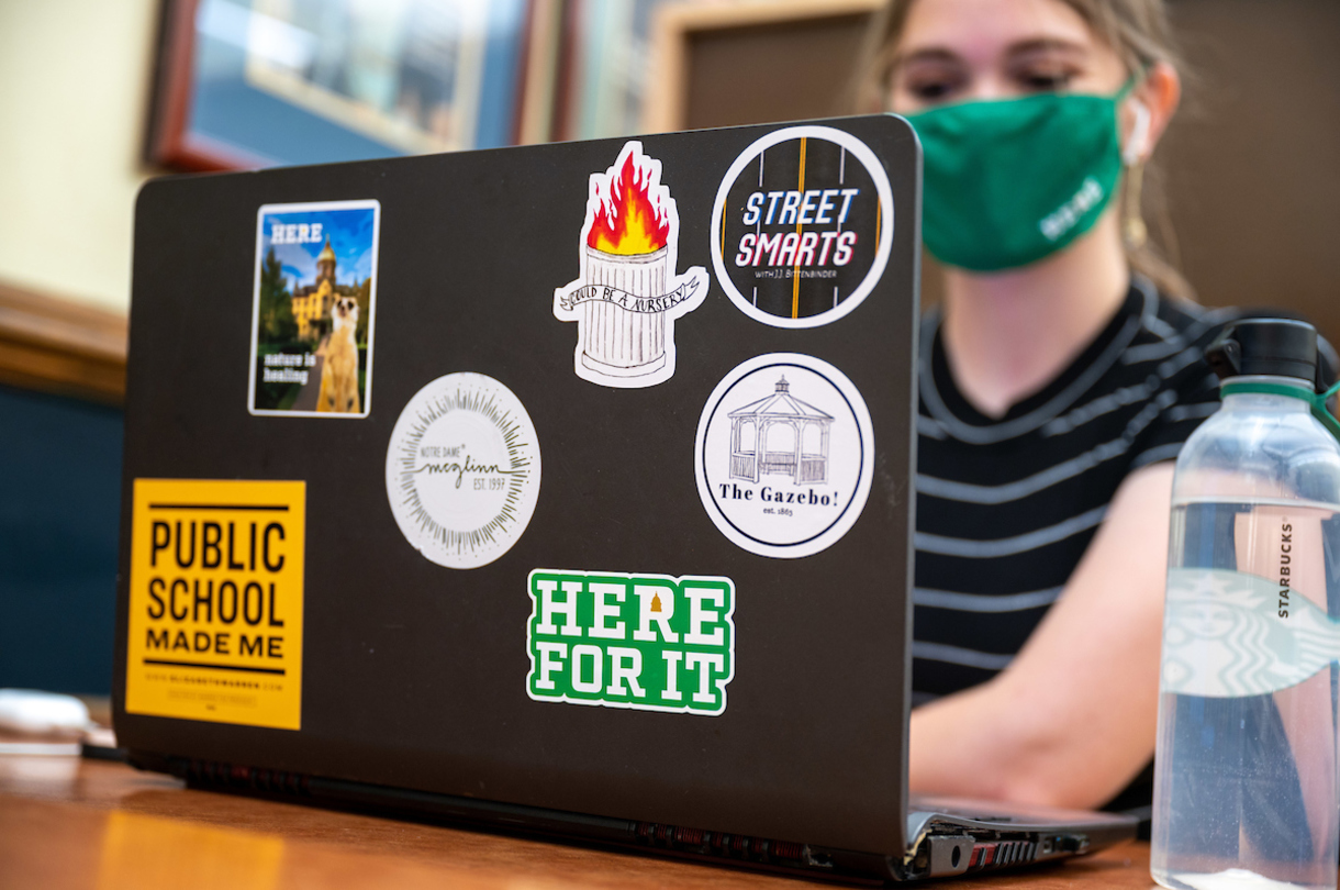Student sitting at laptop with stickers on the top that include one that says