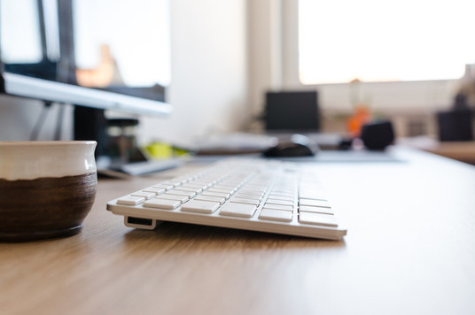 Photo of a keyboard on a desk in an office.
