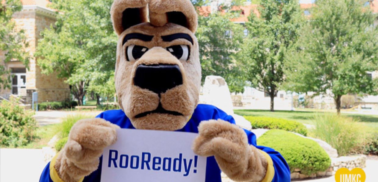 KC Roo on campus holding up a sign that says RooReady!