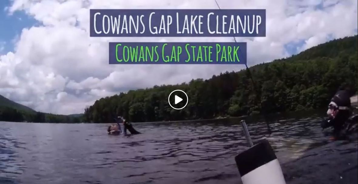 Divers in scuba gear float on the surface of a lake. Text: Cowans Gap Lake Cleanup, Cowans Gap State Park