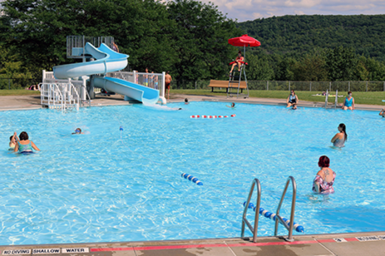 A large swimming pool full of water and some people with a water slide and lifegaurd