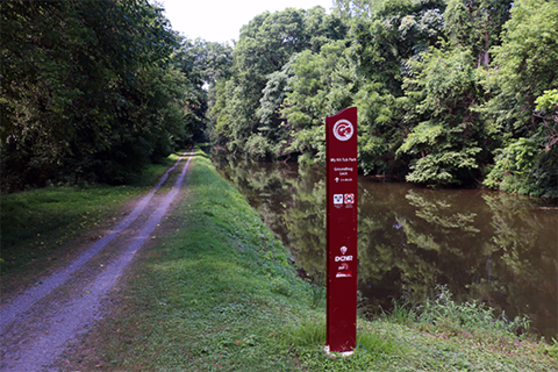 A red sign post stands between a grassy trail and a canal full of water with trees all around.