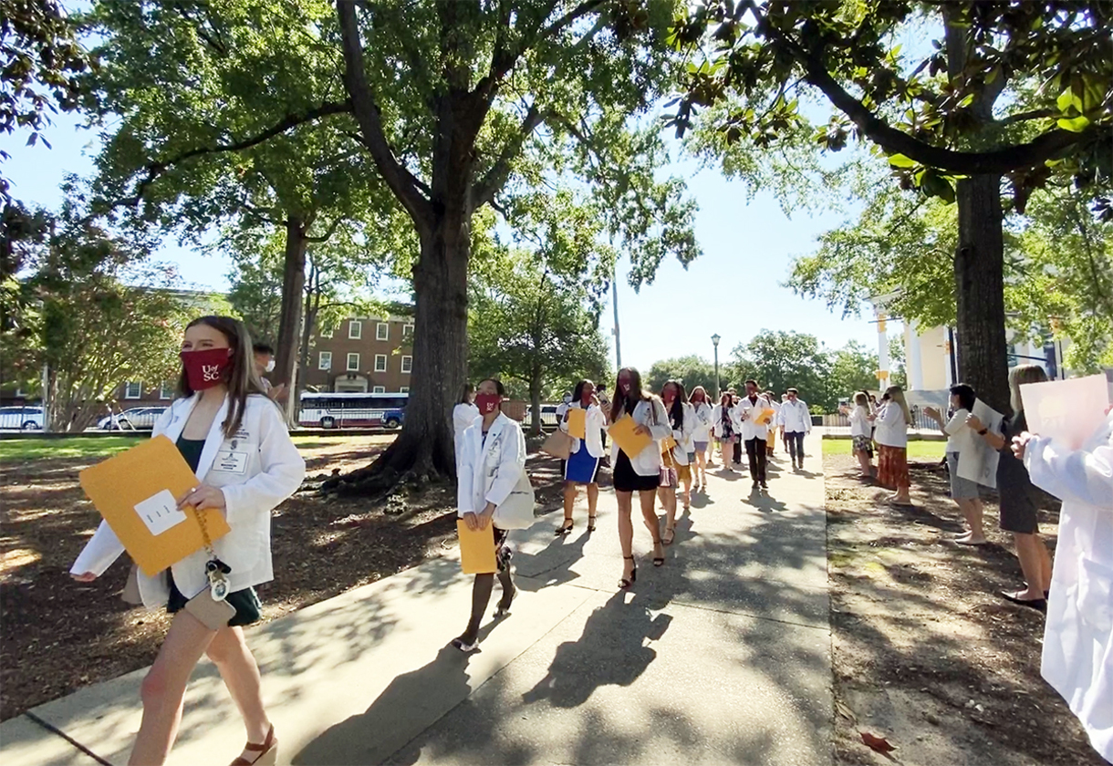 Pharmacy students in white coats and masks