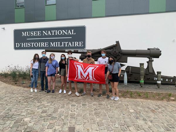Students with Miami flag in front of a piece of artillery at the museum in Diekirch