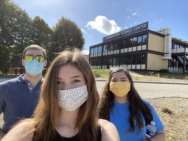 three students in masks in front of the Science Center