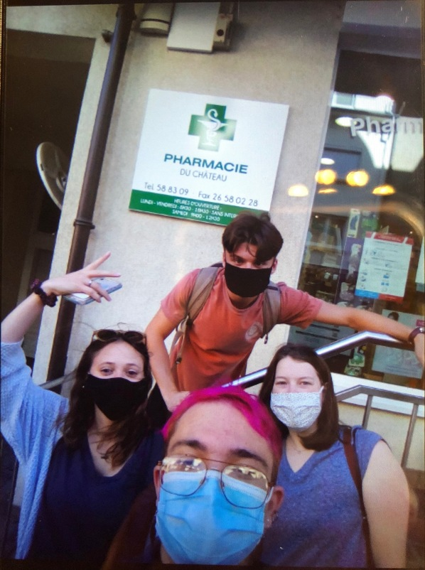 4 students in masks in front of a pharmacy