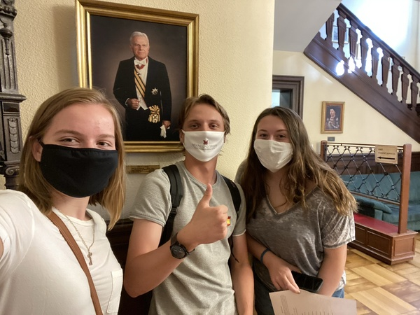 Three students in masks in the chateau in front of a photo fo Ambassador Dolibois