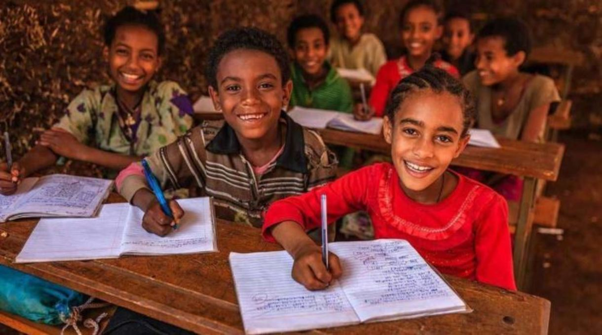 Photo of school-aged children writing in notebooks