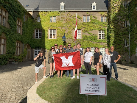 Students pose with a Miami M flag in front of chateau, with a welcome sign in 3 languages