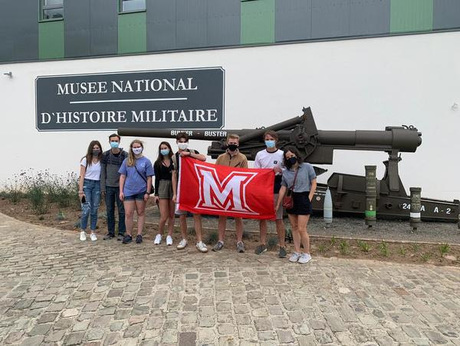 Students pose with M flag outside Musee National D'Histoire Militaire