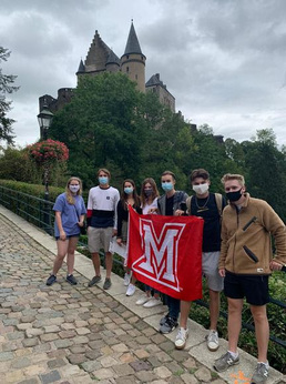 Students pose with M flag in Vianden, with castle visitble in background