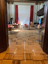 Entrance to hall with directional arrows to maintain social distancing