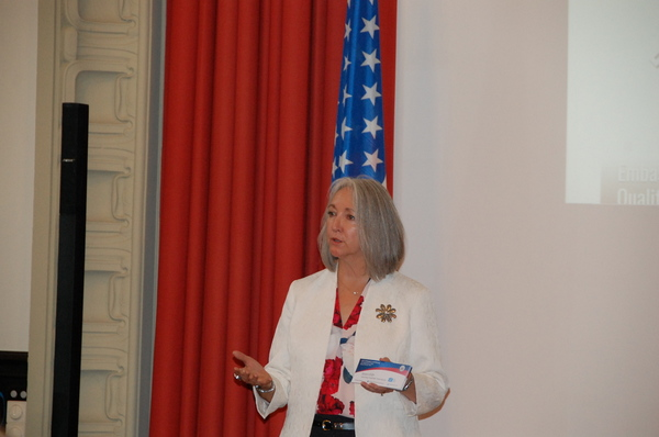 Woman speaking in front of American flag