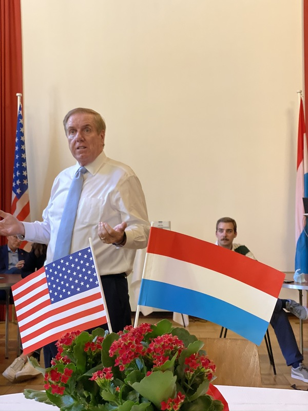 Man speaking behind US and Luxembourg flags