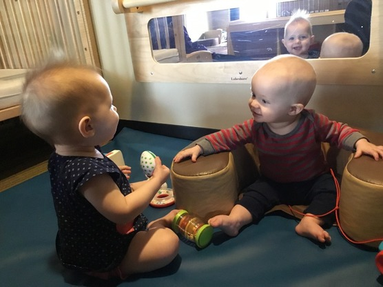 Two infants interacting with toys together
