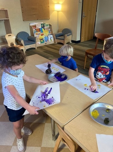 Group of preschool boys painting together