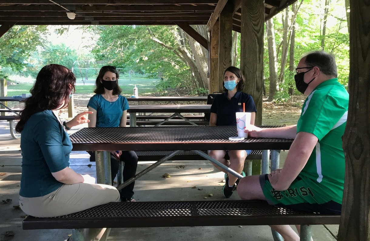 Photo of people wearing face masks, seated at a picnic table.