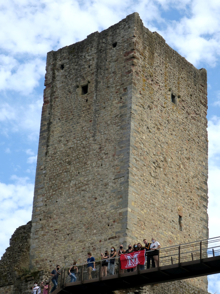 Students on a castle bridge with a tower in the background