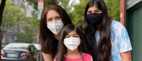Kavita Daiya and her two daughters wearing masks
