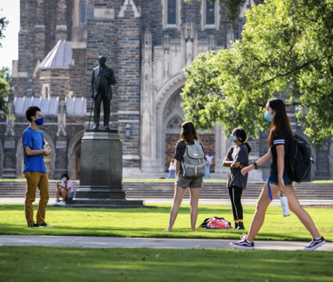 Students stand talking socially distanced on Duke's campus