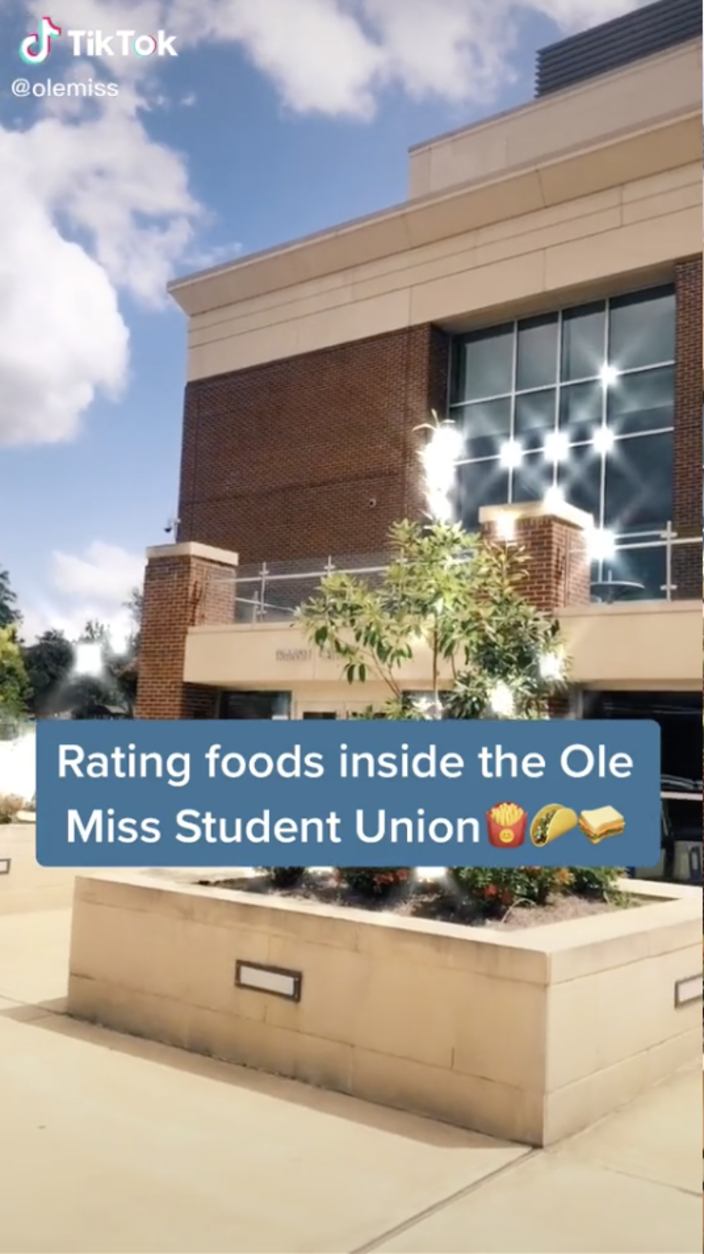 Still from a TikTok video featuring the back entrance of the Student Union and the text