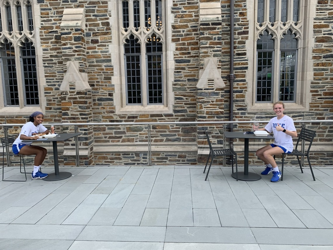 Two students practicing proper physical distancing while eating a meal together.
