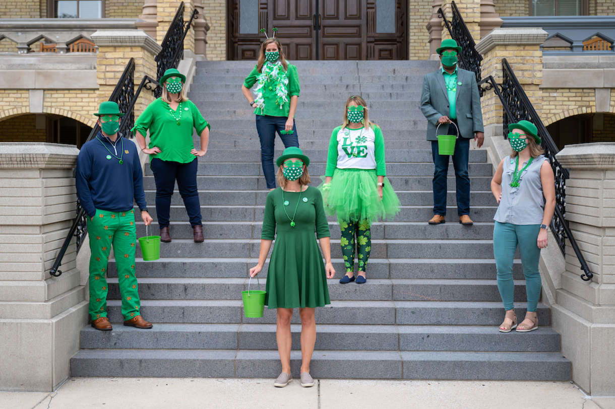 University Enterprises and Events leaders, wearing green, stand on the steps of Main Building.