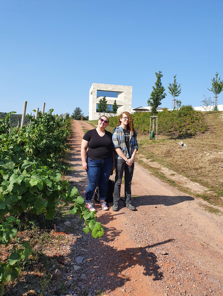 Two students in vineyards with an open building behind