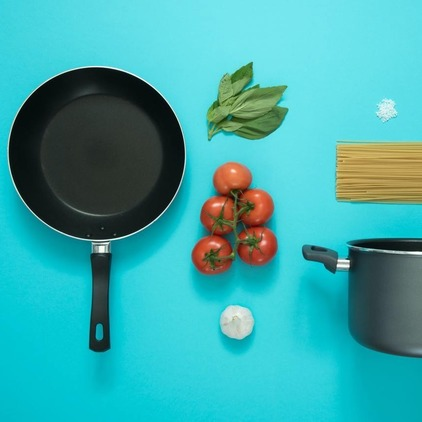 Pasta ingredients laid out on blue backdrop.