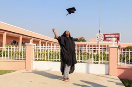 A female recent graduate wearing a graduation gown throwing her cap into the air.