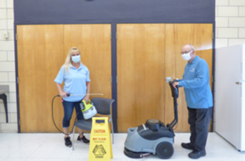 Janitorial workers using a floor cleaner and other cleaning devices.