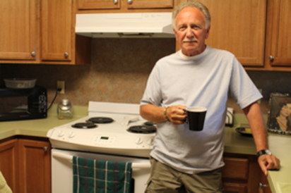 A senor living resident in his kitchen drinking coffee.