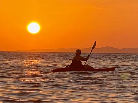Sunset view of Ali operating kayak on the lake