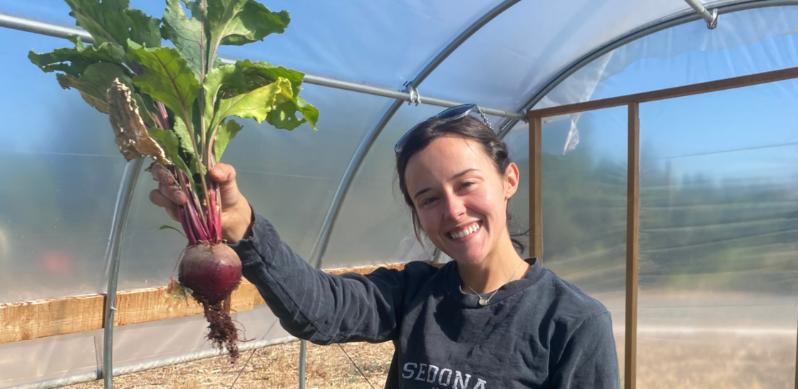 Standing in a greenhouse, Grace Sonderman holds up a