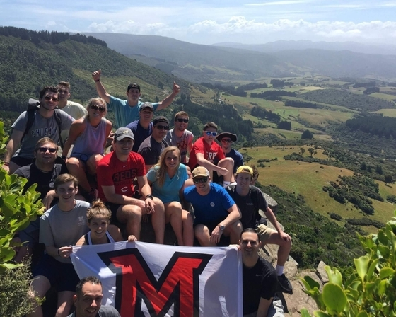 Study abroad students pose on a mountainside with Miami M flag