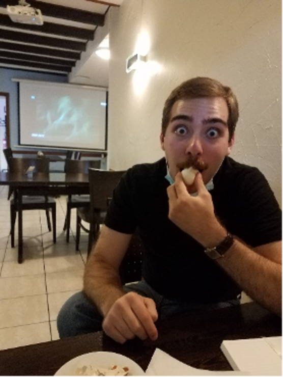 man eating an egg in a cafe with a TV in the background