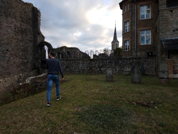 man walking on grass between buildings