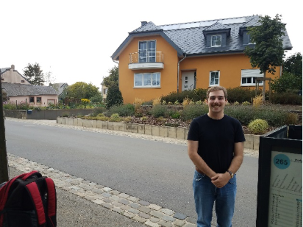 Man at bus stop with house behind