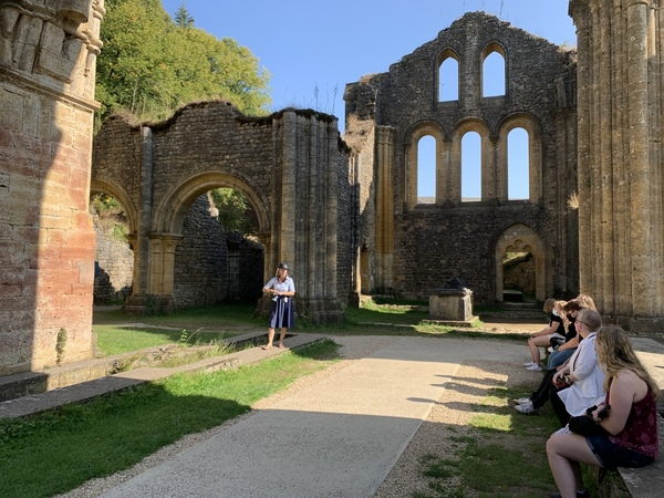 Students listening to a tour guide inside of open air ruins
