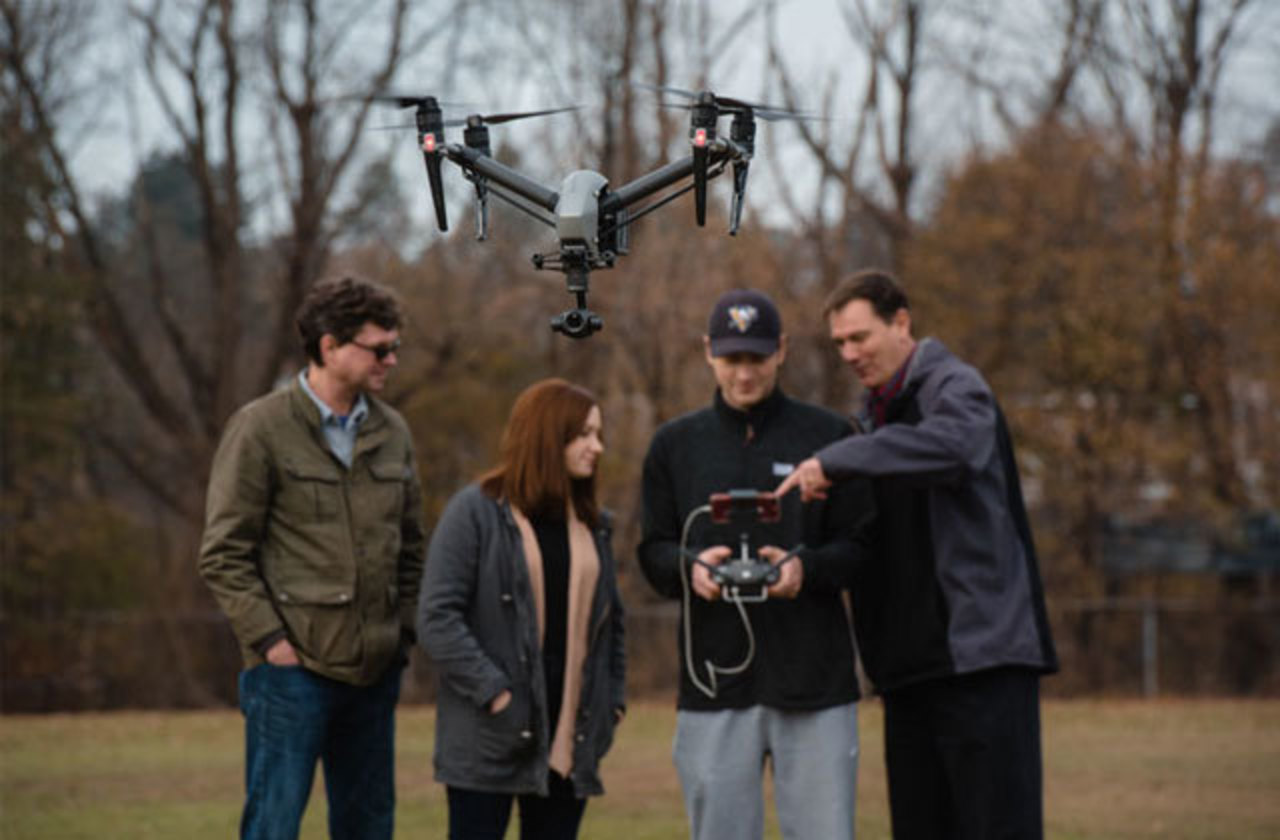 Faculty members Christopher Schaney and John Benhart flying a drone with students Kate Marodi and Jordan Hudzicki