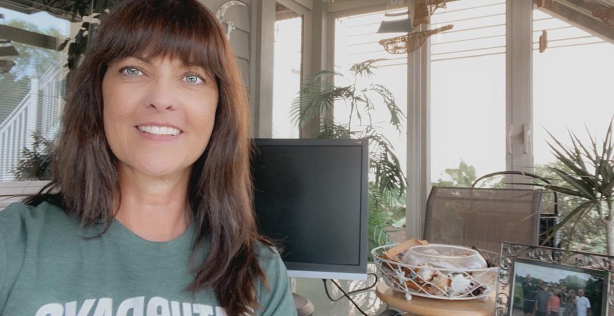 Photo of Heather Christensen in her sunroom where she sometimes works.