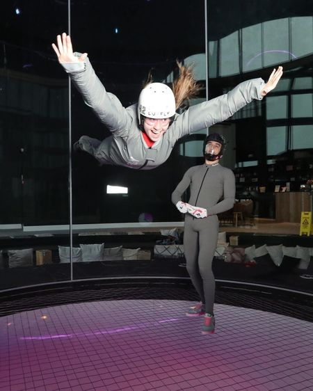 Woman floating on air with trainer in background