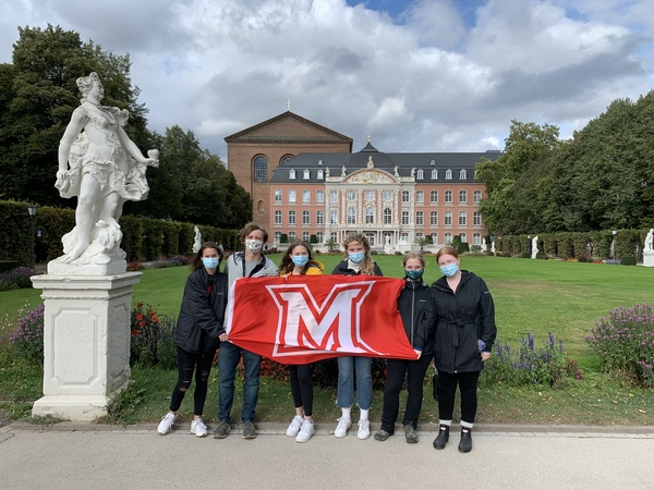 Students with flag next to a statue with palace and basilica behind